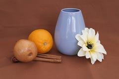 Natura morta con un vaso, una frutta e un fiore blu fotografia stock