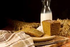 Natura morta con una brocca di vetro di latte, pane di segale, spighe del granoturco Fotografie Stock