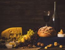 Natura morta con vino, l'uva, il pane e le varie specie di formaggio Immagine Stock