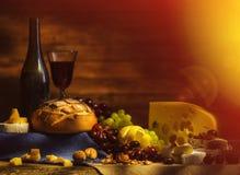 Natura morta con vino, l'uva, il pane e le varie specie di formaggio Fotografia Stock