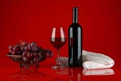 Natura morta con vino rosso, l'uva e l'asciugamano bianco immagini stock libere da diritti