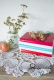 Natura morta d'annata con i libri, gli orologi, la mela ed il vaso con i fiori sul centrino Immagini Stock Libere da Diritti