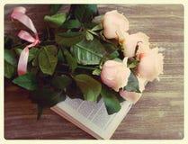 Natura morta d'annata delle rose e del libro su legno Fotografie Stock