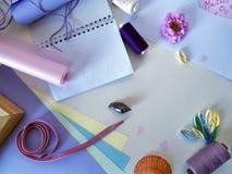 Natura morta degli elementi del cucito in tavolozza lilla su un fondo leggero per la festa Fotografie Stock Libere da Diritti