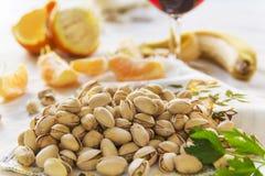 Natura morta dei pistacchi, peases dell'arancia e un bicchiere di vino Fotografie Stock