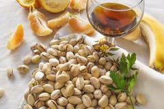 Natura morta dei pistacchi, peases di arancio e un vetro del wiskey Fotografia Stock