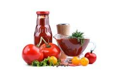 Natura morta dei pomodori rossi e gialli, della bottiglia di salsa al pomodoro e dell'aneto su un fondo bianco Un oggetto isolato Immagine Stock
