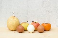 Natura morta del gruppo e dell'uovo della frutta su compensato e sul muro di cemento Immagine Stock Libera da Diritti