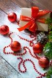 Natura morta del ` s del nuovo anno con i giocattoli del contenitore di regalo e del ramo e di festa di albero dell'abete su neve immagini stock libere da diritti