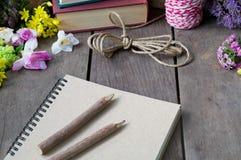 Natura morta del taccuino intorno ai fiori piacevoli sulla tavola di legno Fotografie Stock Libere da Diritti