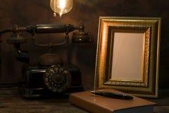 Natura morta del telefono d'annata con la cornice ed il diario sopra Fotografie Stock