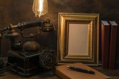 Natura morta del telefono d'annata con la cornice ed il diario sopra Fotografia Stock Libera da Diritti