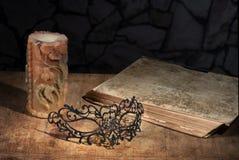 Natura morta dell'annata con la maschera, il libro e la candela Immagini Stock Libere da Diritti