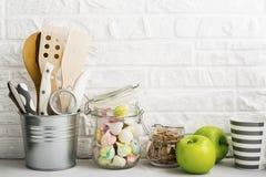 Natura morta della cucina su un fondo bianco del muro di mattoni: vari taglieri, strumenti, verdi per la cottura, ortaggi freschi Immagini Stock