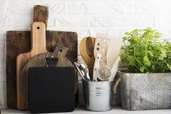 Natura morta della cucina su un fondo bianco del muro di mattoni: vari taglieri, strumenti, verdi per la cottura, ortaggi freschi Fotografia Stock