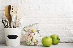 Natura morta della cucina su un fondo bianco del muro di mattoni: vari taglieri, strumenti, verdi per la cottura, ortaggi freschi Immagine Stock