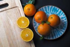 Natura morta delle arance sul tagliere di legno con il piatto blu, b Fotografie Stock