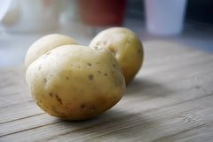 Natura morta delle patate crude su una tavola di legno immagini stock libere da diritti
