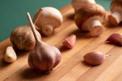 Natura morta di aglio e dei funghi presentati su un bordo di legno immagini stock libere da diritti