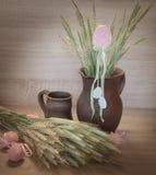 Natura morta di Easters dalle uova dipinte, grano crudo Fotografia Stock Libera da Diritti