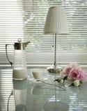 Natura morta di estate con la brocca, le lampade di lettura, la tazza e le peonie su una tavola di vetro Fotografia Stock