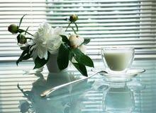 Natura morta di estate con la tazza e le peonie su una tavola di vetro Fotografia Stock Libera da Diritti