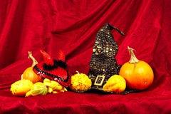 Natura morta di Halloween con le zucche, il cappello della strega e un cappello di rosso del diavolo Fotografia Stock