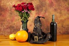 Natura morta di Halloween con le zucche, vino, con il cappello ed i fiori fotografie stock