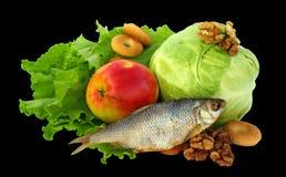 Natura morta di lattuga, cavolo, frutta secca, mela, essiccazione, pesce essiccato, dadi e secco apricotsIsolated su fondo nero Immagine Stock