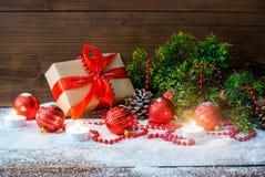 Natura morta di Natale con i giocattoli del contenitore di regalo e del ramo e di festa di albero dell'abete su fondo di legno fotografie stock