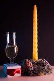 Natura morta di Natale su fondo nero, candela gialla, Immagini Stock