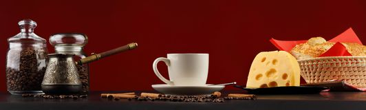 Natura morta di panorama con una tazza di caffè, un formaggio e un panino su un fondo di Borgogna immagini stock