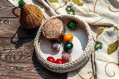 Natura morta di Pasqua come la brocca e pottle tricottato con le uova colorate dentro i soggiorni sulla tavola di legno invecchia immagini stock libere da diritti