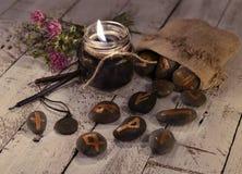 Natura morta di predizione con le candele nere e le rune antiche sulle pietre Immagine Stock Libera da Diritti