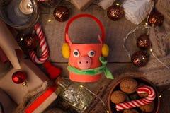 Natura morta di umore di Natale su un fondo di legno con un simbolo di un maiale diy da 2019 anni, del contenitore di regalo feli fotografia stock