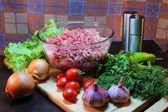 Natura morta di una tazza con le verdure crude e le erbe della carne tritata Fotografia Stock