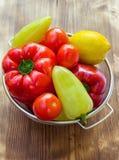 Natura morta di verdure dei peperoni, pomodori, limone in ciotola del setaccio Immagine Stock
