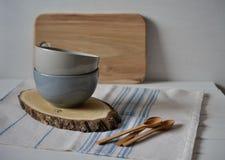 Natura morta domestica semplice della cucina su un fondo delle pareti luminose su una tavola di legno Fotografie Stock Libere da Diritti