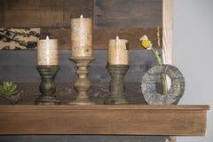 Natura morta rustica dei supporti e delle candele di candela di legno e un fiore che si siede su un manto contro un fondo di legn immagine stock