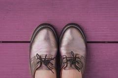 Natura morta in scarpe di cuoio alla moda del ` s delle donne di colore porpora con i pizzi su un bordo di legno porpora fotografia stock