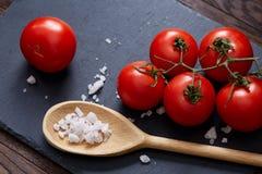 Natura morta vegetariana con i pomodori, il pepe ed il sale freschi dell'uva in cucchiaio di legno su fondo di legno, fuoco selet Fotografia Stock Libera da Diritti