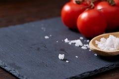 Natura morta vegetariana con i pomodori, il pepe ed il sale freschi dell'uva in cucchiaio di legno su fondo di legno, fuoco selet Fotografie Stock Libere da Diritti