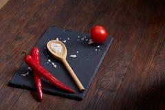 Natura morta vegetariana con i pomodori, il pepe ed il sale freschi dell'uva in cucchiaio di legno su fondo di legno, fuoco selet Immagini Stock