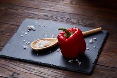 Natura morta vegetariana con i pomodori, il pepe ed il sale freschi dell'uva in cucchiaio di legno su fondo di legno, fuoco selet Fotografie Stock