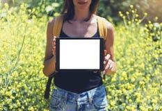 Natura widoku modnisia mienie w ręki pastylki komputerze Dziewczyna podróżnik używa gadżet na słońce kolorze żółtym i racy kwitni zdjęcie stock