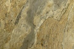 Natural abstract background. The texture of the old yellow stone wall with chinks royalty free stock image