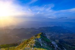 Natural alpine scenery landscape of mountains and strong contrast warm and blue colors. Breathtaking panoramic view of Bran area. Between the Piatra Craiului stock image