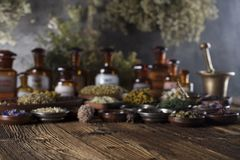 Natural and alternative medicine.  Place for logo and text. Herbs in bowls, mortar and medicine bottles on wooden rustic table Stock Images