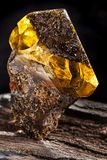 Natural amber stone. A piece of dirty amber with transparent yellow layer on piece of stoned wood. A piece of dirty amber with transparent yellow layer, has royalty free stock photography