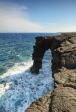 Natural arch in the black lava rock cliffs. Natural arch i(Holei sea arch) in the black lava rock cliffs, Hawaii Volcanoes National Park.  This view is at the Royalty Free Stock Photography